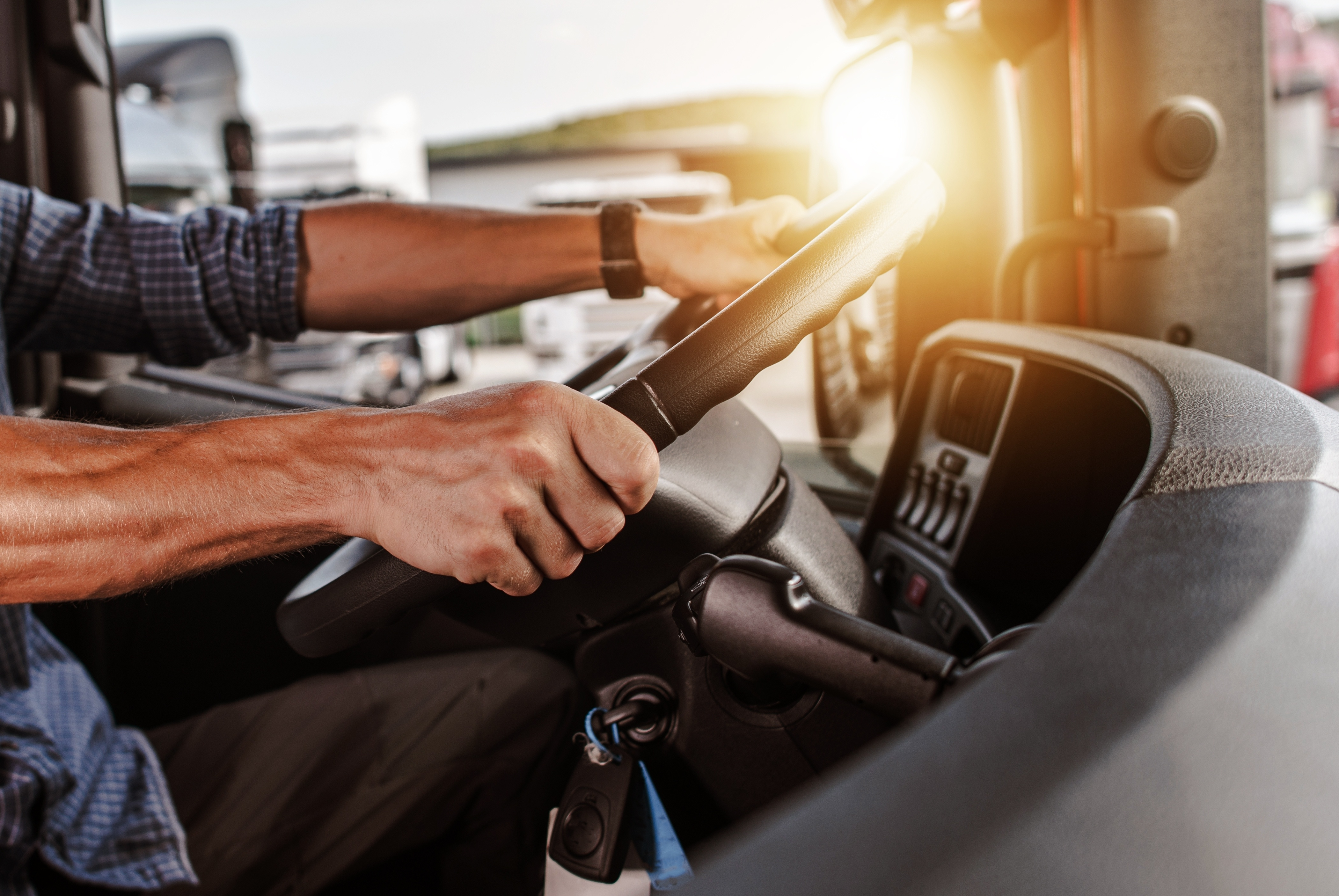 Close up of truck driver holding steering wheel