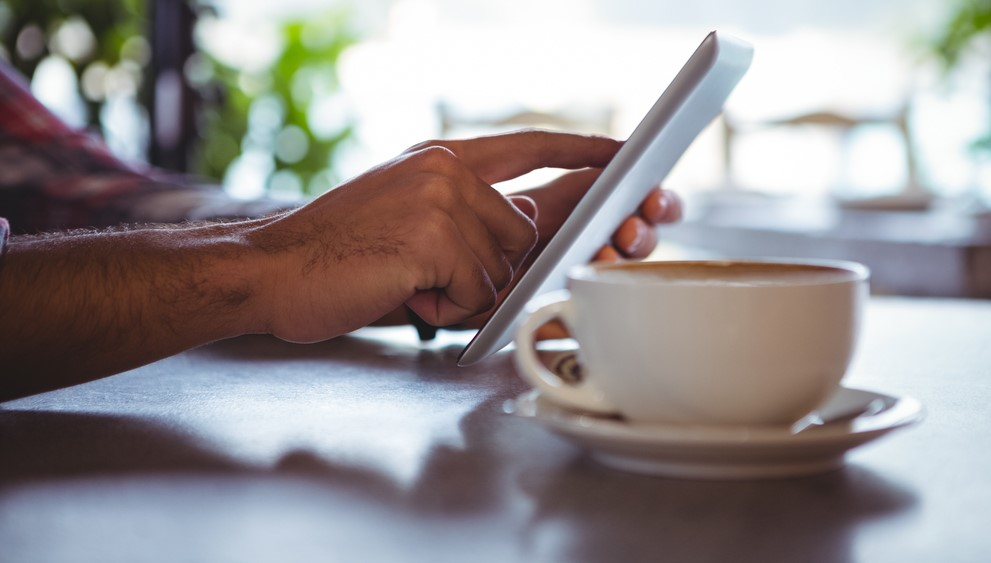 Hands of man using digital tablet in cafeteria 2