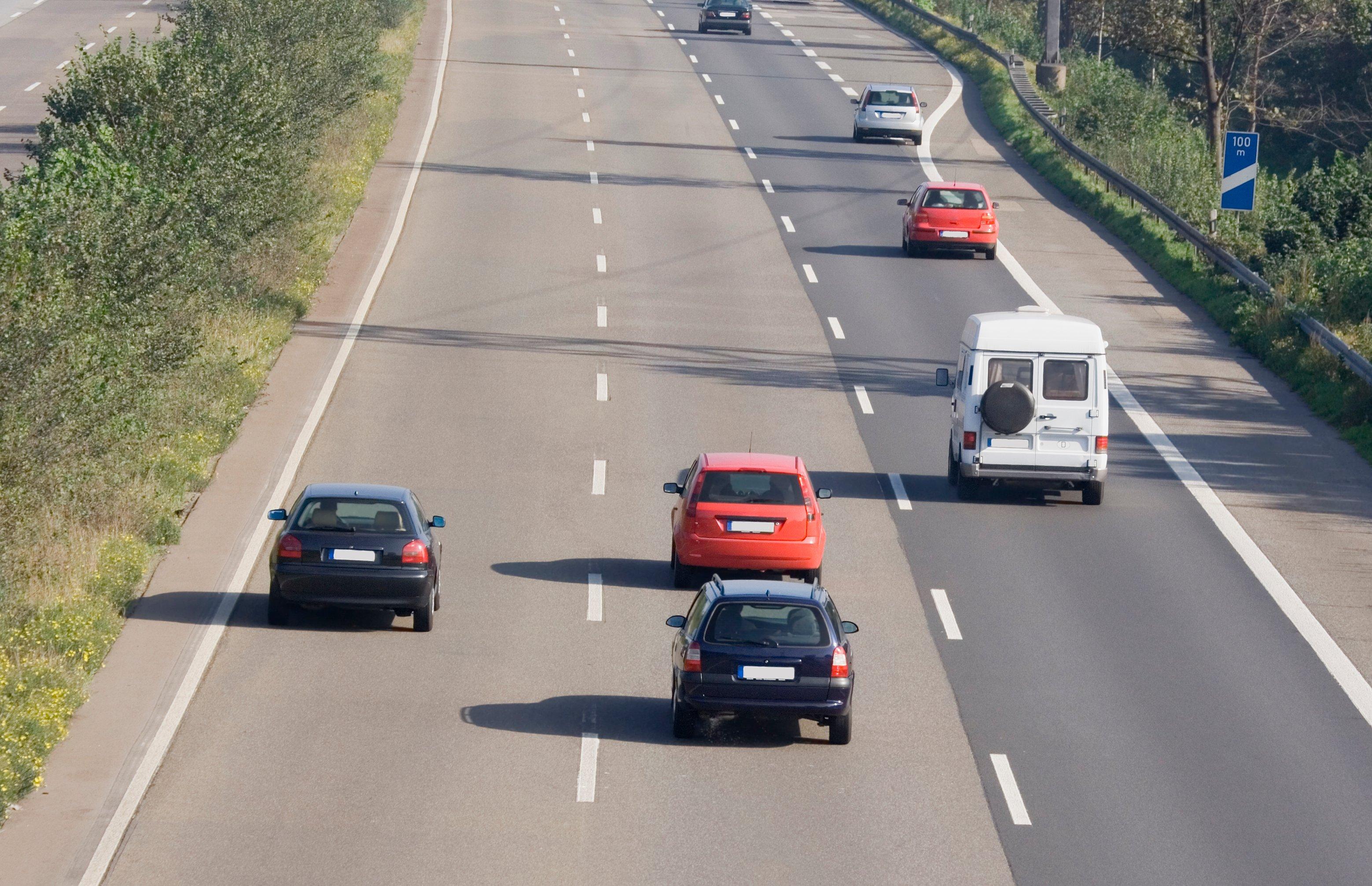 cars traveling on three-lane road