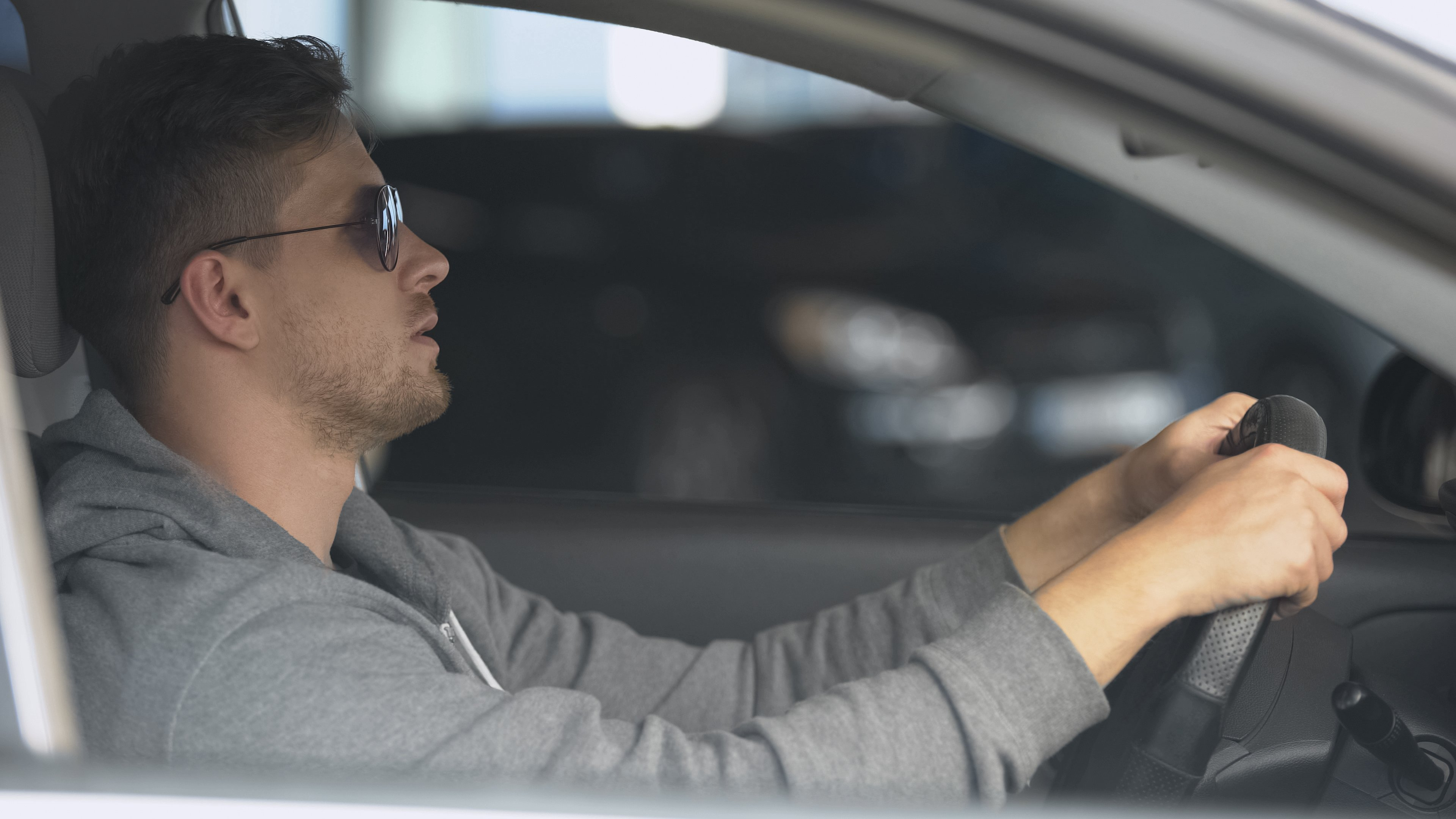 Man in sunglasses driving under the influence